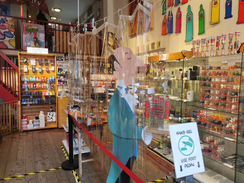Veilig winkelen in de Condomerie: een groot plastic scherm en een voetpompje met handgel. Beeld Juliët Boogaard