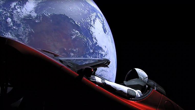 Een pop genaamd StarMan en gehuld in een ruimtepak van SpaceX zit achter het stuur van de Tesla Roadster die dinsdag werd gelanceerd naar een baan om de zon. Beeld afp