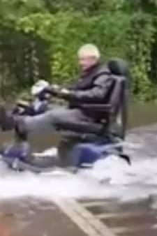 Oudere man scheurt met scootmobiel door plassen in Hengelo