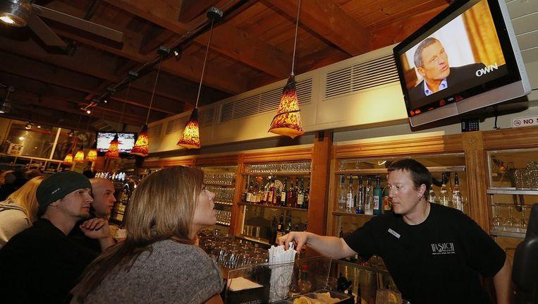 Amerikanen kijken in een pub naar het interview met Lance Armstrong. Beeld EPA