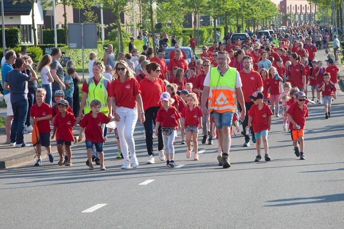 In een lange stoet lopen de deelnemers aan de jeugdavondvierdaagse door Woerden.