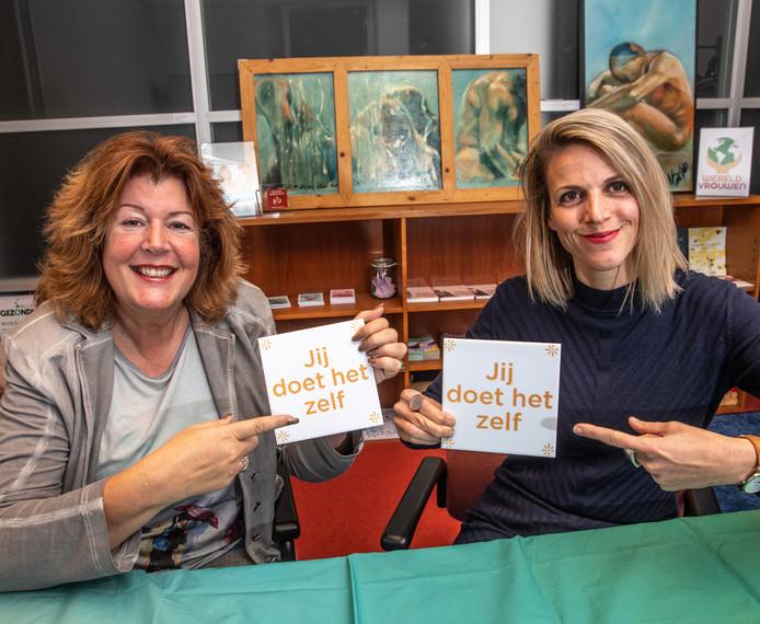 Voorzitter van Vrouwenplatform Carree Janine van Harsselaar (links) en bureaucoördinator Jojanne Lageveen wijzen naar een slogan die de organisatie gebruikt om meer vrouwen aan het werk te krijgen.