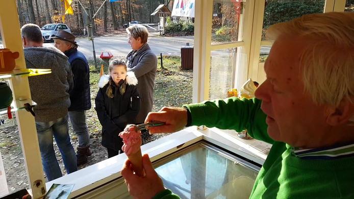 John van Barneveld schept een ijsje voor een jonge bezoekster van de Kiosk Hertenkamp in Epe.