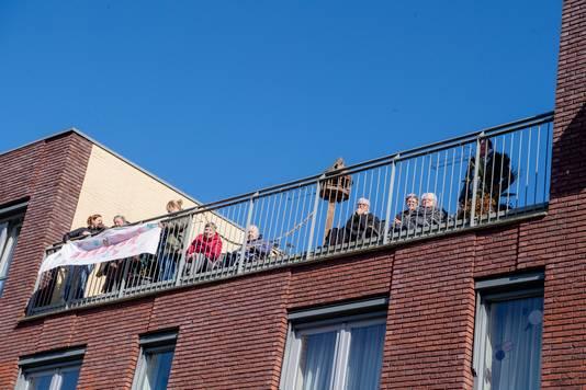 En dat zingen werd gewaardeerd. Veel ouderen zochten het gezamenlijke balkon op.