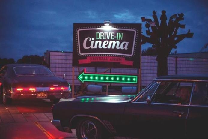 In je auto kijken naar een film bij de openluchtbioscoop.