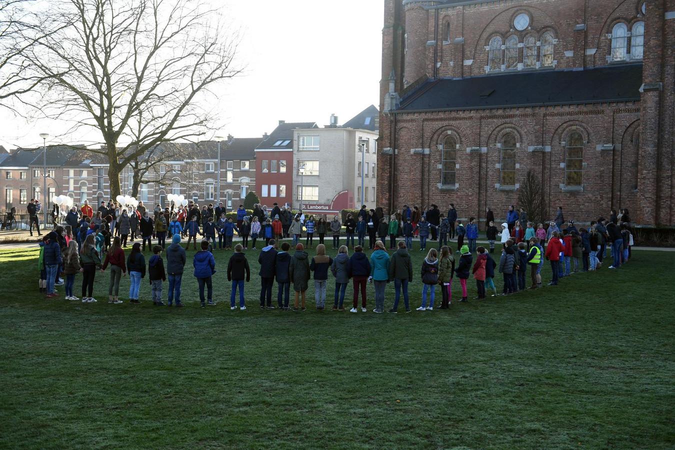 De leerlingen, ouders en leerkrachten van de Sint-Lambertusschool staan in een kring op het kerkplein van Heverlee.