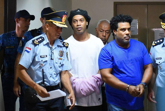 Ronaldinho en zijn broer Roberto Assis (r) arriveren geboeid bij de rechtbank in Asunción.