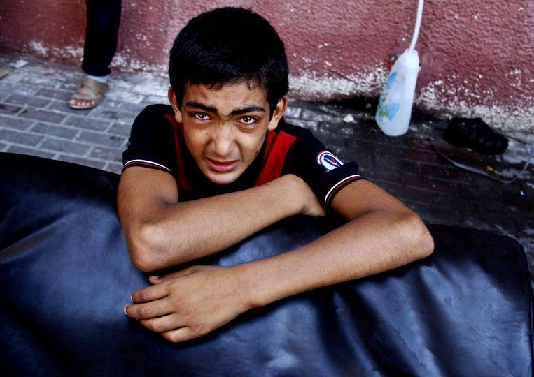 Een Palestijnse jongen huilt na een Israëlische luchtaanval in het zuiden van de Gazastrook. Beeld ap