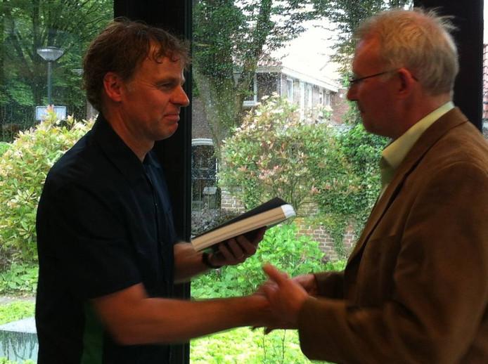 Winy Maas biedt wethouder Peter Roozendaal het boek aan.
